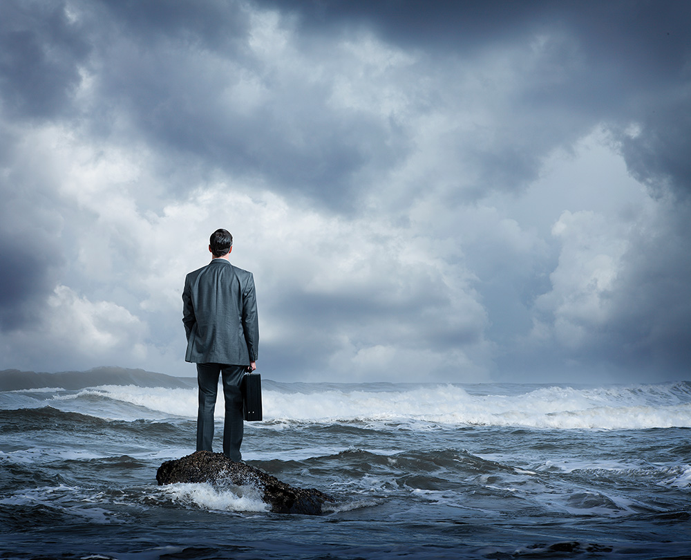 Businessman Standing In Rough Ocean Surf - Worth